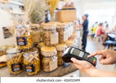 hand holding credit card machine on Coffee shop blur background