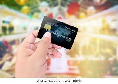 Hand holding credit card on blurred abstract background