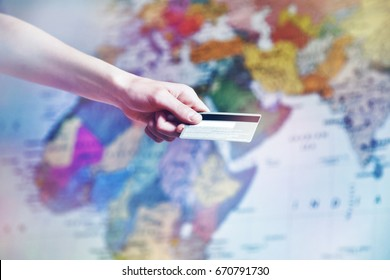 Hand holding credit card on world map background. Online shopping, booking and international paying concept