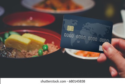 Hand holding Credit card on Japanese food in restaurant. Use credit card to pay for food. Shopping concept.