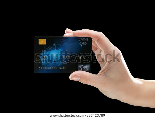 Hand holding credit card on black background
