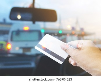 Hand holding credit card over blurred background of car cockpit at pay toll station on tne traffic jam evening.