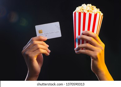 Hand holding credit card and popcorn. Movie ticket payment.