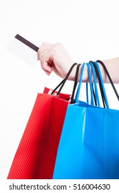 Hand holding credit or debit card and bunch of shopping bags isolated on white background
