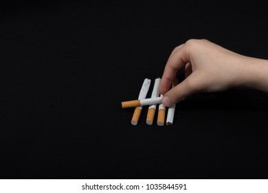 Hand is holding crossed cigarettes on black background