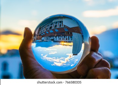A hand holding a crystal ball for optical illusion. City as the background. Known as an orbuculum, is a crystal or glass ball and common fortune telling object. Performance of clairvoyance and scrying