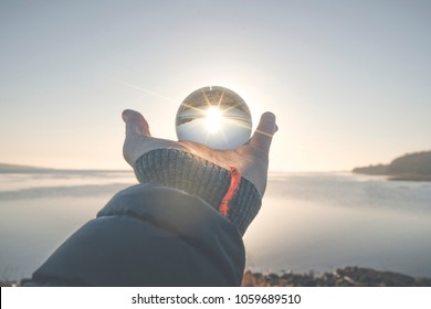 Hand holding a crystal ball in the winter sunrise by a lake in the morning