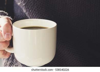 Hand holding a cup of coffee selective focus