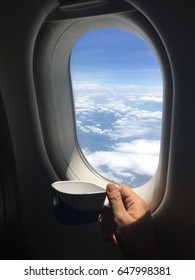 Hand holding cup of tea  sky window of airplane