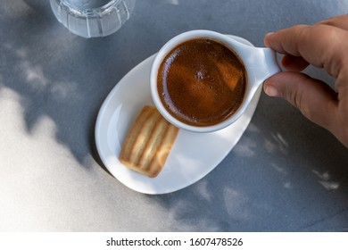 hand holding Cup of traditional Turkish coffee served with one biscuit and glass of water on a sunny day