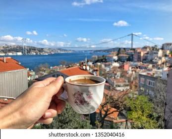 hand holding a cup of turkish coffee against Bosporus Bridge in Istanbul, Turkey