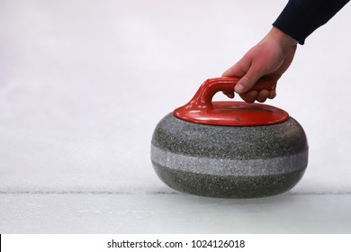 Hand holding curling stone