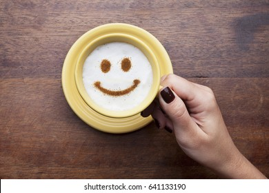 Hand holding a cute yellow cup with coffee cream. Food art creative concept image, happy face drawing with cinnamon powder over wooden background.