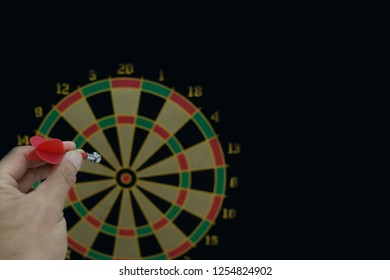 The hand holding the dart while aim at the dartboard.