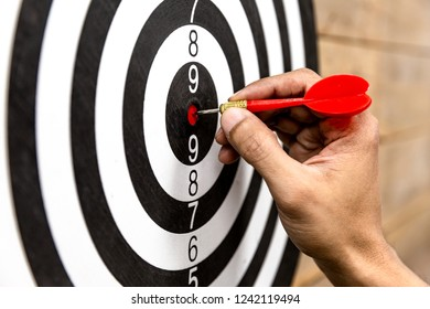 hand holding darts and stabbing or puncturing on dart board.Business target or goal success and winner the marketing concept.free space.