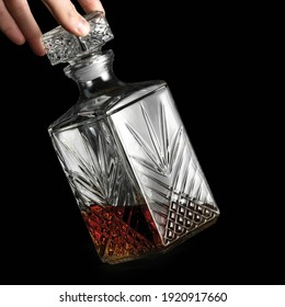 Hand holding a decanter with whiskey on a black background