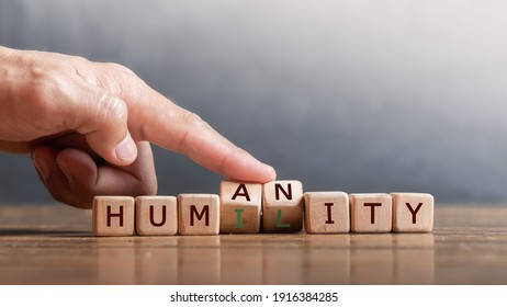 """hand holding dice with text for illustration of """"Humanity and Humility"""" words"""