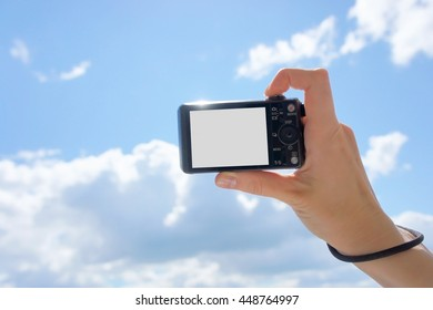 Hand holding digital camera against the sky. Empty space for your picture or text.