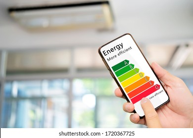 Hand holding digital smartphone and looking at house efficiency rating. Detail of house efficiency rating on digital tablet screen. Concept of ecological and bio energetic house. Energy class.