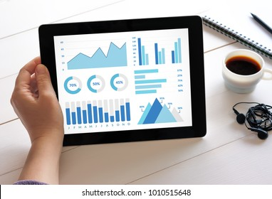 Hand holding digital tablet computer with graphs and charts elements on screen. All screen content is designed by me