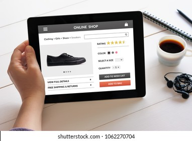 Hand holding digital tablet computer with online shop concept on screen. All screen content is designed by me