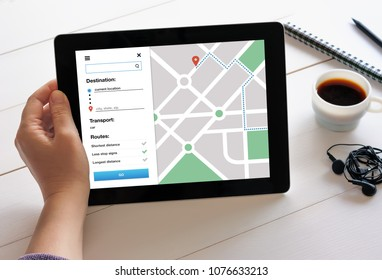 Hand holding digital tablet computer with GPS map navigation app on screen. Location tracker concept