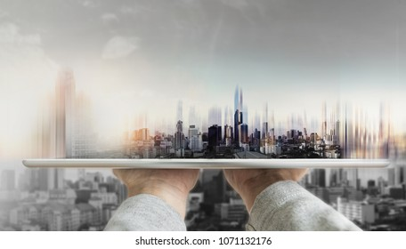Hand holding digital tablet with futuristic modern buildings hologram on screen