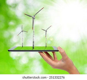 Hand holding digital tablet with a wind turbines.  Green energy concept.
