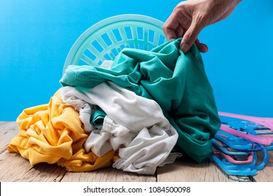Hand holding dirty laundry in washing basket on wooden plank,blue background