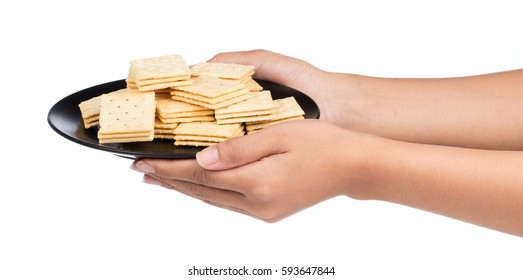 hand holding dish of Tasty biscuits isolated on white background