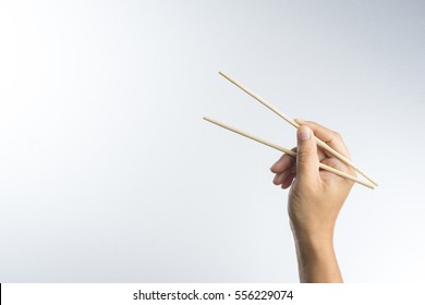 Hand holding disposable wooden chopsticks made of bamboo on white background