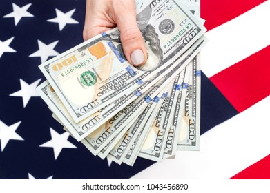 Hand holding dollar bills over background of american flag.