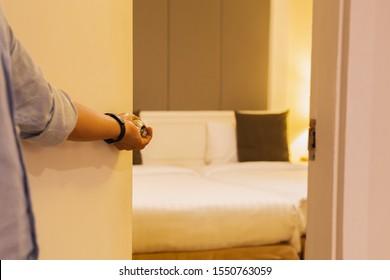 Hand holding door knob, opening hotel bedroom door selective focus.