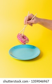 A hand holding a doughnut with chopsticks on a yellow background