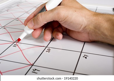 A hand holding a dry erase marker X'ing out or crossing out days of the month on a calendar.  Passing of time concept