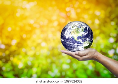 Hand Holding Earth with Abstract Green Leaves Bokeh Background, Suitable for Saving World and Environment Concept. Elements of This Image Furnished by NASA.