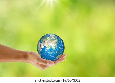 Hand holding the earth on natural bokeh background. save the earth concept.