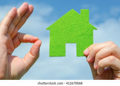 Hand holding eco house icon concept and other hand showing ok sign on the blue sky with clouds background