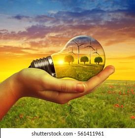Hand holding eco light bulb with wind turbines at sunset. The concept of sustainable resources.