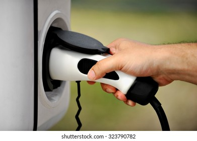 Hand holding an electric plug in for charging electric car