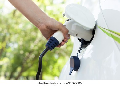 Hand holding an electric plug-in for charging electric car