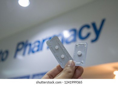 A hand holding emergency contraception (morning after pill) packs with pharmacy text background.