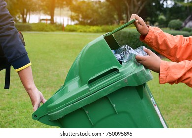 Hand holding empty bottle into the trash, volunteer concept