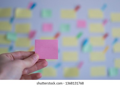 A hand holding empty pink sticky note in front of a kanban board