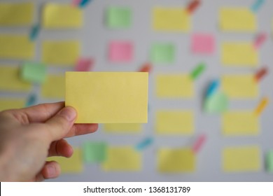 A hand holding empty sticky note in front of a kanban board