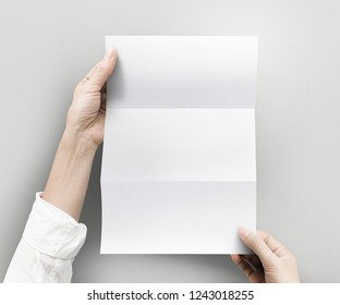 Hand holding empty white blank paper sheet A4 size on grey background.