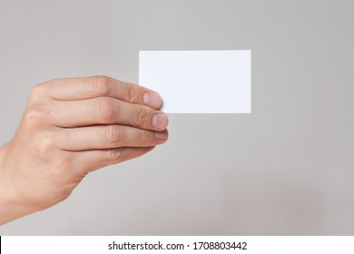 Hand holding empty white business card.