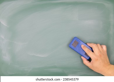 Hand holding the eraser to clean the blackboard