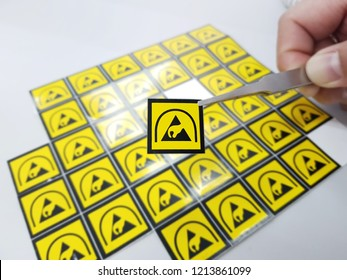 Hand holding ESD symbol label with tweezers,Electrostatic Sensitive Devices (ESD) in electronic industrial.