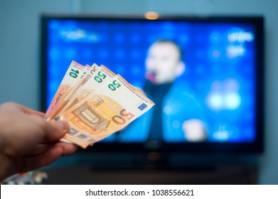 Hand holding euro money in front of tv